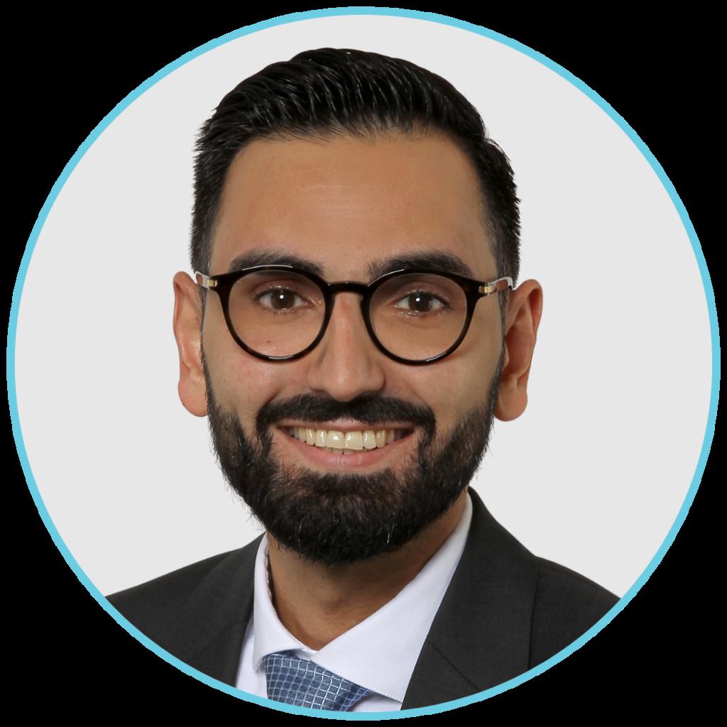 Auf diesem Bild ist Karim Fereidooni frontal zu sehen. Man sieht ihn bis zu den Schultern. Er trägt eine Brille und einen Anzug.
