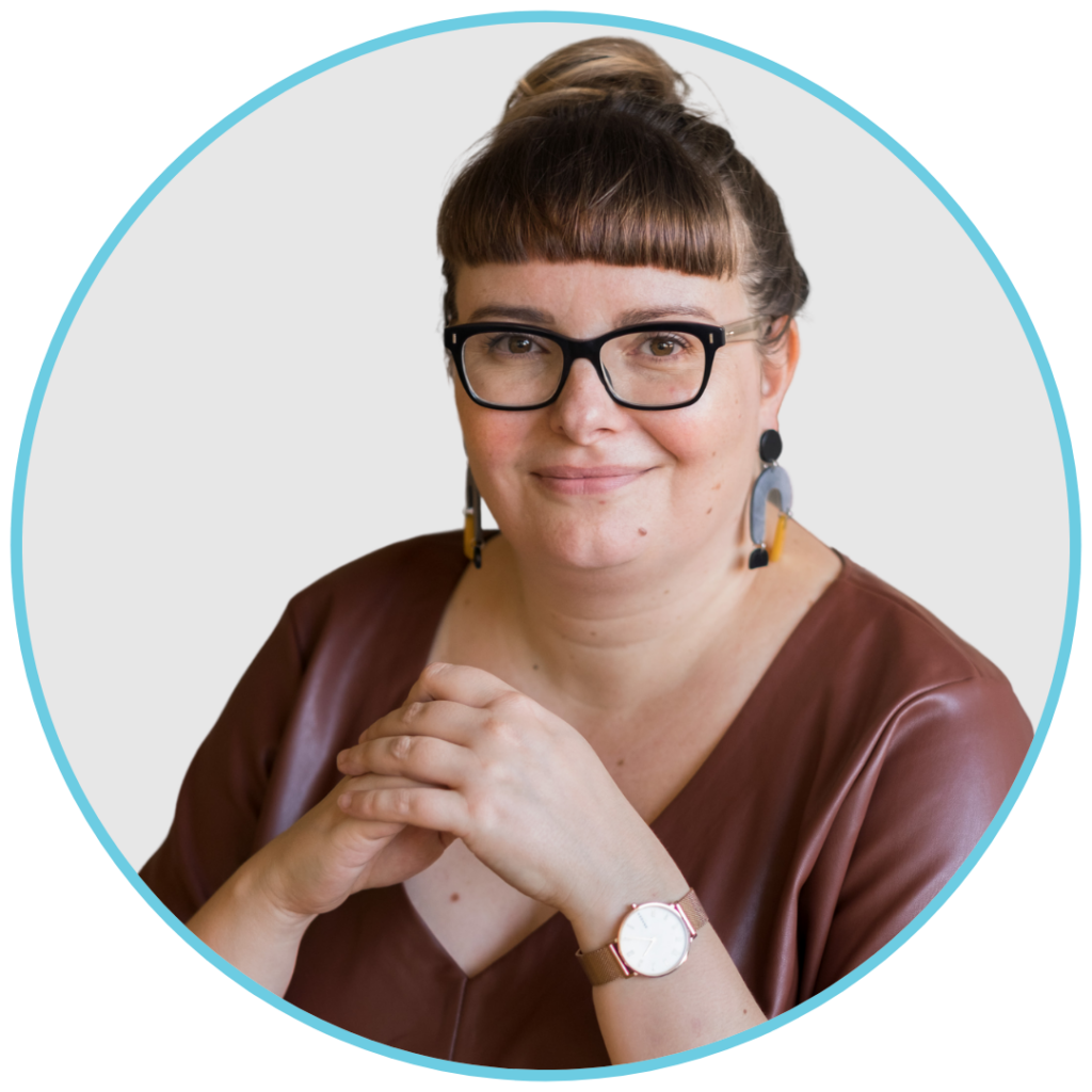 Auf diesem Bild ist Melanie Bittner zu sehen. Sie trägt eine braune Bluse, eine Brille und Ohrringe und sitzt mit zusammengefalteten Händen an einem Tisch.