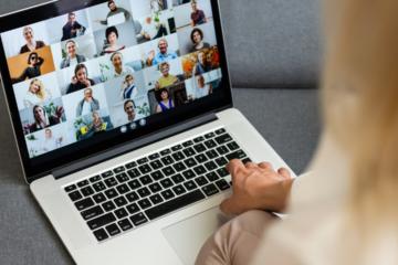 Eine blonde Frau sitzt an einem Laptop und schaut einen Online Vortrag an.